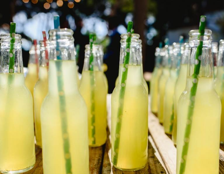 Paper straws in bottles of a beverage.